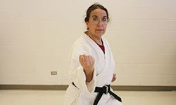 A lady completing karate forms with her arms